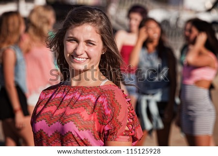 Smiling young European girl with friends in the background - stock photo