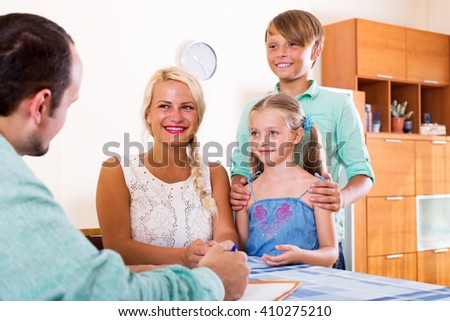 Smiling young family and male advisor sitting at desk with documents