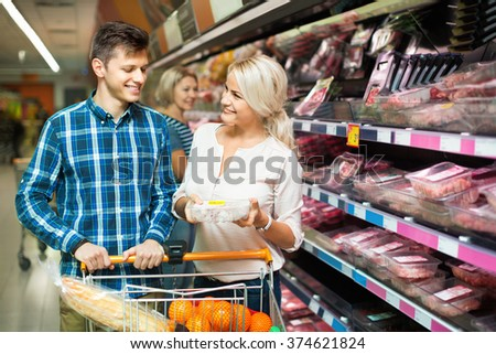 Smiling young family couple choosing chilled meat in food store - stock photo
