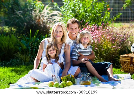 Smiling young family having picnic in a park - stock photo