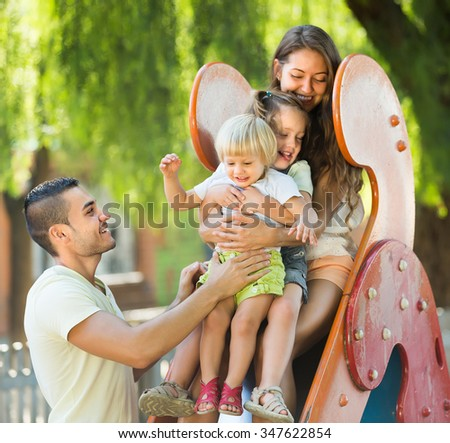 Smiling young family of four at children's playground in summer park. Focus on girl