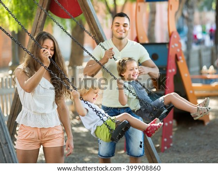 Smiling young family of four at playground's swings. Focus on woman