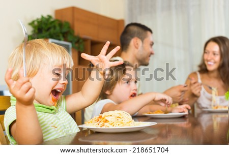 Smiling young family of four having lunch with spaghetti at home. Focus on girl - stock photo