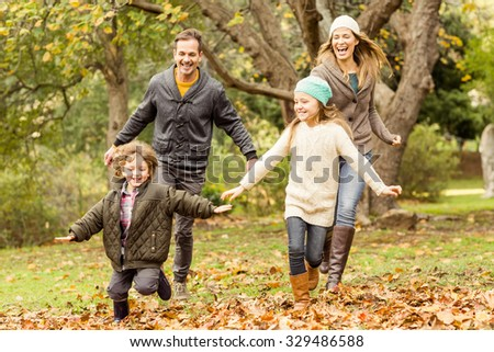 Smiling young family running into leaves on an autumns day - stock photo