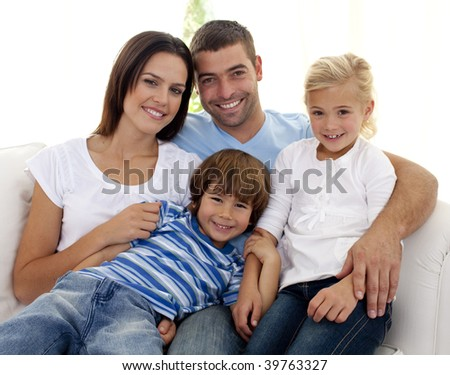 Smiling young family sitting on sofa at home - stock photo