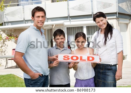 Smiling young family with a sold sign standing outside their new house - stock photo