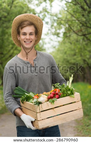Smiling young farmer wearing straw hat and looking at camera. Farmer holding wooden box with fresh vegetables and standing in green garden