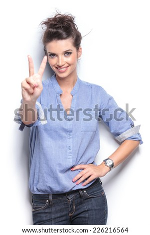 Smiling young fashion woman leaning on a white wall while showing the victory sign. - stock photo