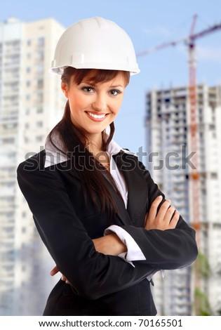 Smiling young female architect holding blueprints - stock photo