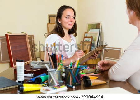 Smiling young female artist  at art studio painting portrait of mature woman - stock photo