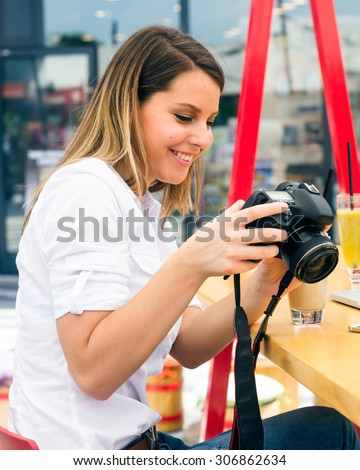 Smiling young female checking photos on her camera at the shopping mall