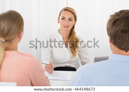 Smiling Young Female Consultant Showing Document To Couple In Office