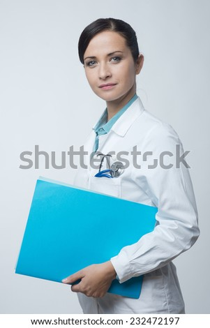 Smiling young female doctor holding medical records file.