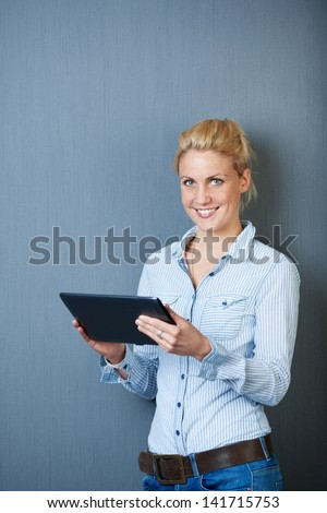 Smiling young female executive using digital tablet against gray background