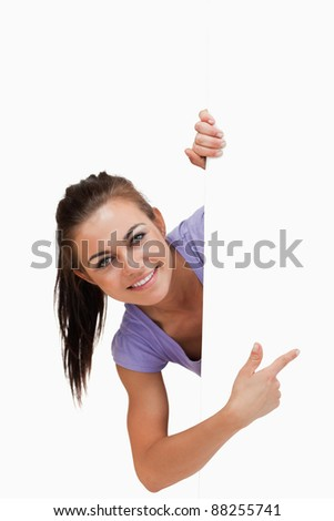 Smiling young female pointing around the corner against a white background - stock photo