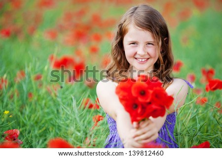Smiling young female showing a red flowers over the flower field background - stock photo