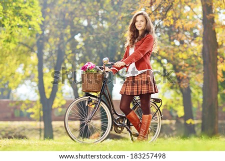 Smiling young female standing with bicycle in park and looking at camera - stock photo