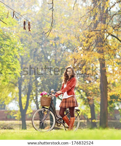 Smiling young female standing with bicycle in park and looking at camera, shot with a tilt and shift lens - stock photo