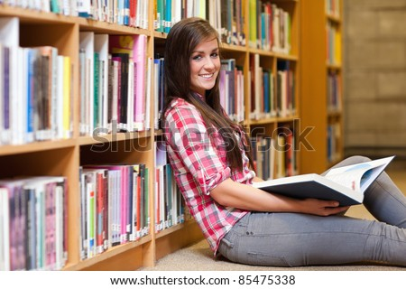 Smiling young female student holding a book in a library - stock photo