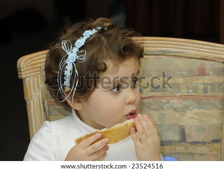 smiling young flower girl at a wedding eating some bread