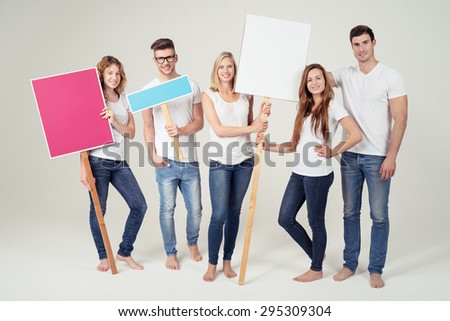 Smiling Young Friends in Casual Clothing, Holding Empty Colored Placard with Copy Space on Off White Background Inside the Studio. - stock photo