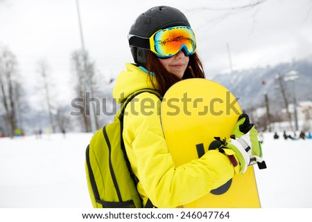 Smiling young gigl holding snowboard - stock photo