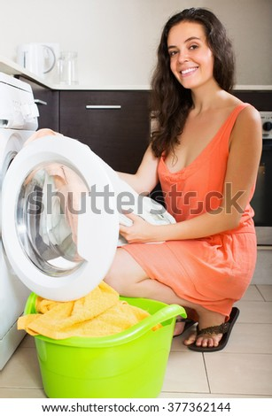 Smiling young girl cheking white clothes near washing machine  at home - stock photo