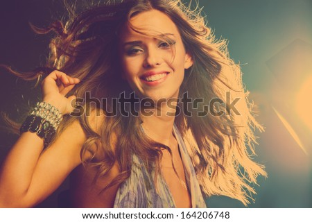smiling young girl dancing in night club, retro colors - stock photo