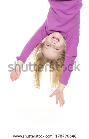 Smiling young girl hanging in front of white background - stock photo
