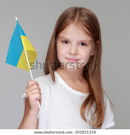 Smiling young girl holding a Ukrainian flag on a gray background/Football Fan - stock photo