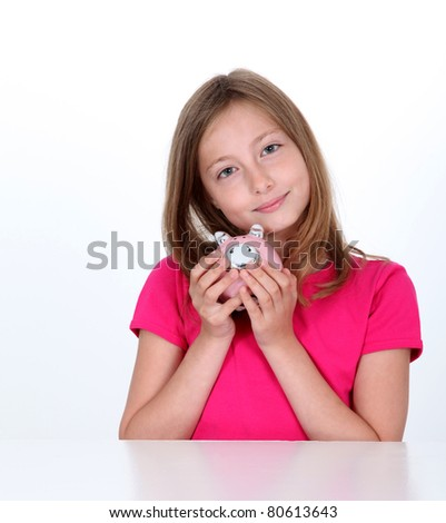 Smiling young girl holding piggy bank