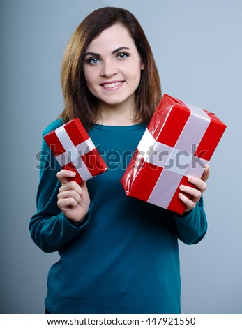 smiling young girl in a blue t-shirt holding gift boxes on gray background