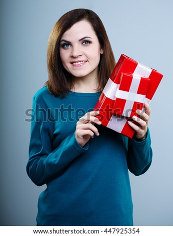 smiling young girl in a blue t-shirt holding gift boxes on gray background - stock photo