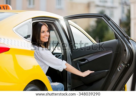 Smiling young girl in a taxi - stock photo