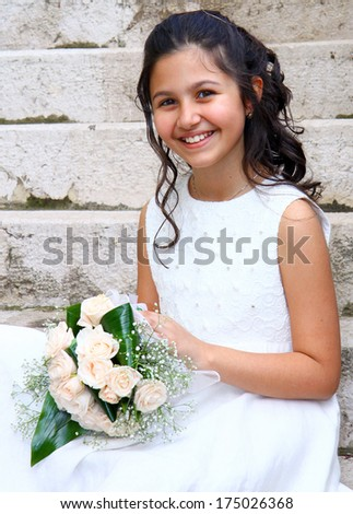 Smiling young girl in white dress for First Communion - stock photo