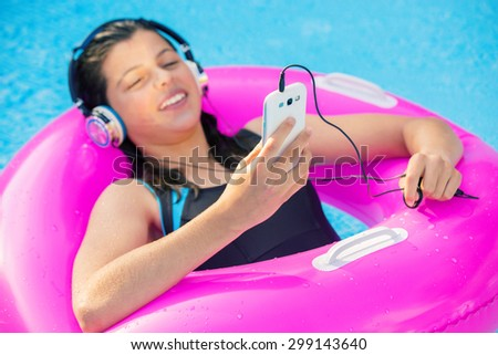 smiling young girl listening to music in a pool with headphones - stock photo