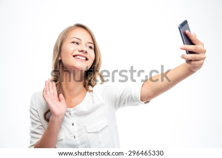 Smiling young girl making selfie photo while waving palm isolated on a white background - stock photo