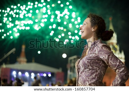 Smiling young girl on a red square next to the Kremlin with fireworks in the sky - stock photo