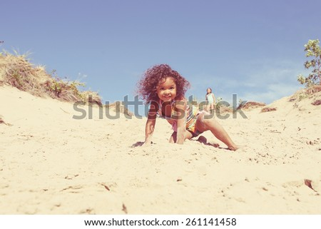 Smiling young girl on sand dune - stock photo