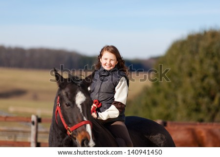 Smiling young girl riding her dark bay horse on a bright sunny day - stock photo