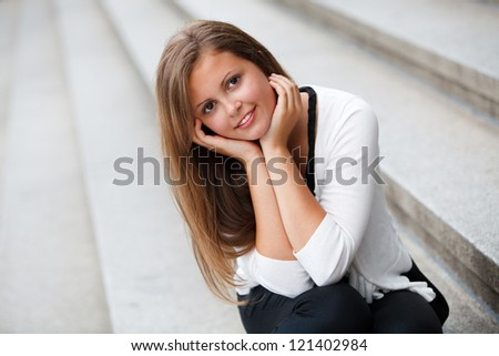 smiling young girl sitting on the steps of - stock photo