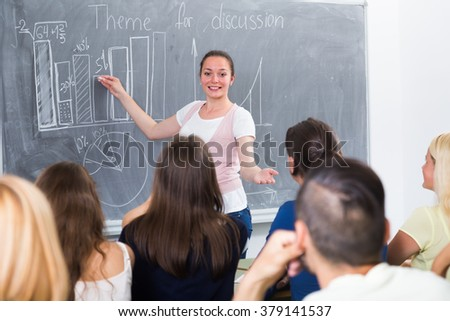 Smiling young girl standing near blackboard in classroom
