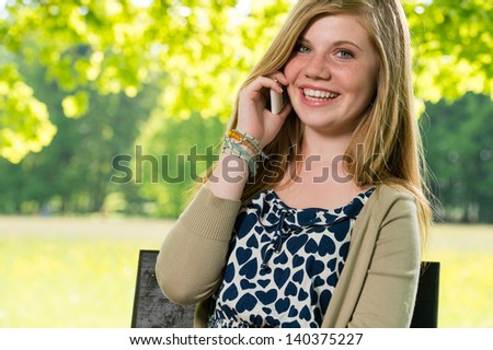 Smiling young girl using her mobile phone outside springtime