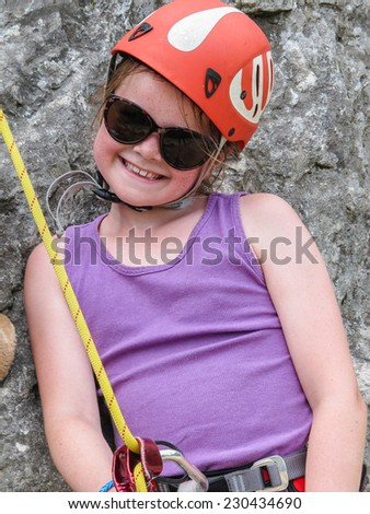 Smiling young girl wearing sunglasses and climbing equipment inlcuding helmet and harness waiting to climb a rock face. - stock photo
