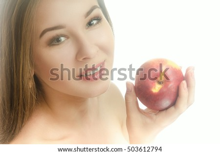 Smiling young girl with a peach in her hand on a white background. Horizontal photo