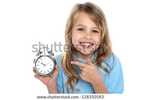 Smiling young girl with an old fashioned clock in hand.