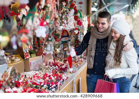 Smiling young girl with boyfriend choosing Christmas decoration at fair. Focus on man - stock photo