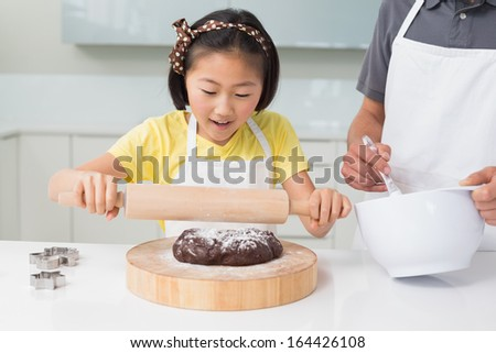 Smiling young girl with her father preparing cookies in the kitchen at home - stock photo
