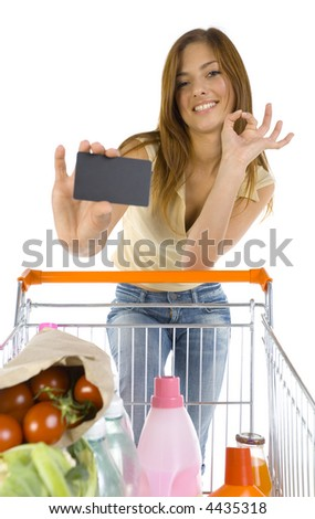 Smiling young girl with trolley. Holding credit card and looking at camera. White background, front view