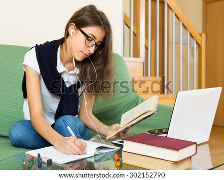 Smiling young girl writing in exercise-book at home